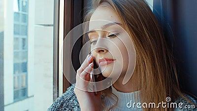 Mujer rubia que habla en el teléfono por la ventana almacen de video