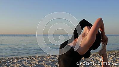 Mujer sana joven de la aptitud en el mono negro que hace yoga por el mar en la salida del sol concepto, disfrute, armonía 4K v?de almacen de video