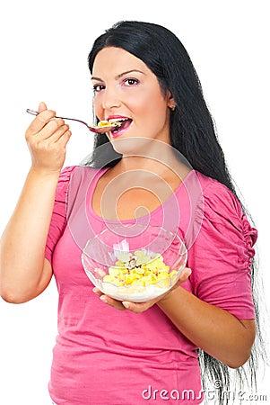 Mujer sana que come los cereales de los copos de maíz