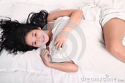 Mujer sensual que duerme en cama