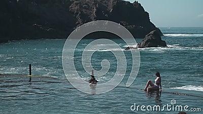 Mujer sentada en el agua del mar almacen de video