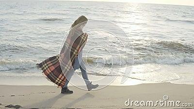 Mujer sola que camina en la playa arenosa con la tela escocesa Tiempo de gasto femenino joven en la orilla del mar en día frío metrajes