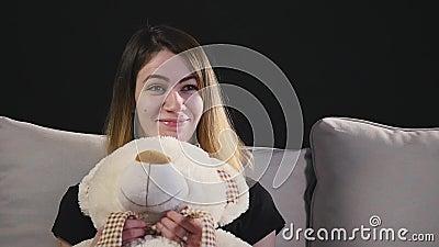 Mujer sonriente bonita que se sienta en el sofá que abraza el oso de peluche almacen de video
