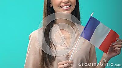 Mujer sonriente con bandera francesa de fondo azul, programa de intercambio estudiantil almacen de video