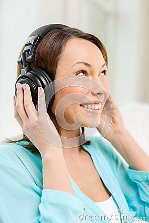 Mujer sonriente con los auriculares en casa