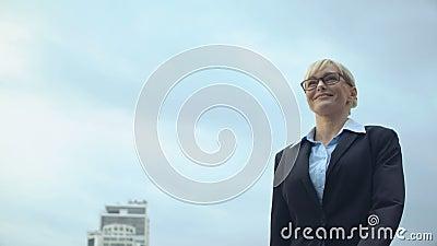 Mujer sonriente en ropa de forma caminando sobre el fondo del cielo, promoción de carrera, éxito almacen de video