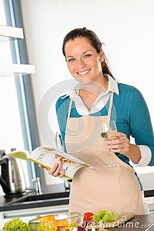 Mujer sonriente que cocina verduras de la receta de la cocina a casa