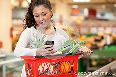 Mujer sonriente que usa el teléfono móvil en almacén de las compras