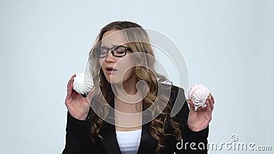 Mujer sosteniendo dos malvavisco y quiere comérselo sobre fondo gris, cámara lenta almacen de metraje de vídeo