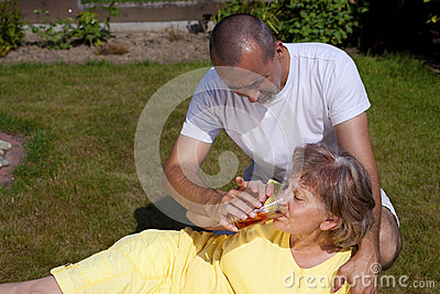 Mujer suministrada hombre con el golpe de calor