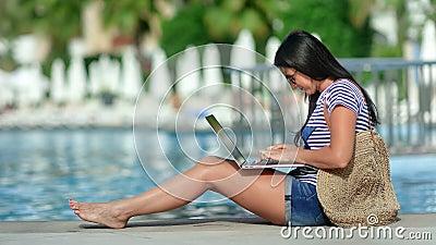 Mujer trabajadora freelancer sonriendo trabajando en un ordenador portátil cerca de la piscina del complejo de lujo almacen de metraje de vídeo