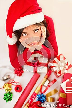 Mujer triste de santa de la Navidad que envuelve los regalos