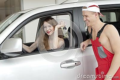Mujer y hombre sonrientes jovenes cerca del coche