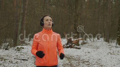 Mujeres con audífonos trotando Mujer joven enfocada en el juego y con mucha actividad en el parque invernal Muchacha haciendo eje almacen de metraje de vídeo
