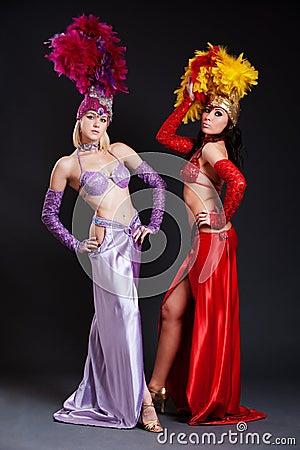 Mujeres hermosas del cabaret en trajes brillantes