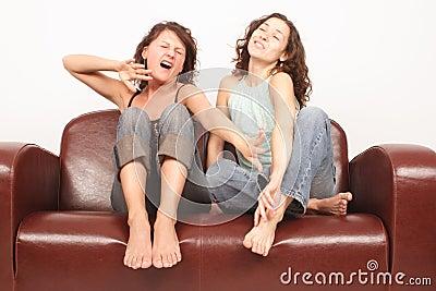 Mujeres jovenes que se sientan en el acabamiento del sofá que ve la TV