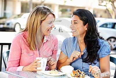 Mujeres que charlan sobre el café y las tortas