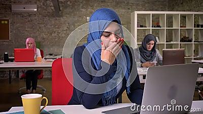 Mulher árabe de bocejo em escuro - o hijab azul trabalhar em seu portátil quando outras fêmeas ias do escritório que sentam-se at video estoque