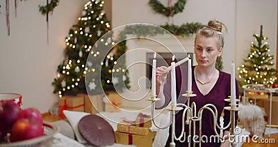Mulher acendendo velas na sala de estar em casa filme