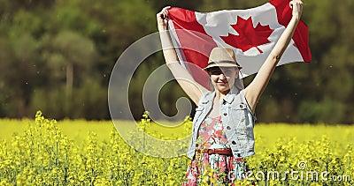 Mulher adulta com bandeira canadense dança em campo de colza no verão video estoque