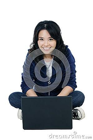 Mulher alegre que senta-se no assoalho com um portátil