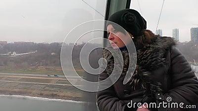 A mulher anda num carro a cabo e olha pela janela vídeos de arquivo