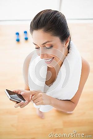 Mulher apta que usa o smartphone que toma uma ruptura do exercício