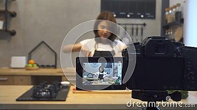 Mulher asiática nova no vídeo da gravação da cozinha na câmera Mulher asiática de sorriso que trabalha no conceito do blogger do  video estoque
