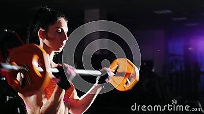 A mulher atl?tica treina os m?sculos das m?os com um barbell halterofilismo f?mea vídeos de arquivo