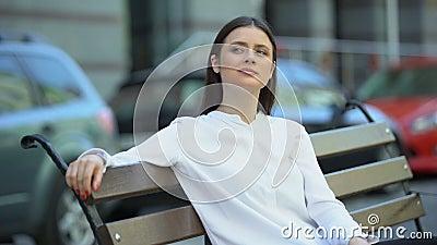 Mulher atrativa desfrutando do freio de trabalho, sentada no banco da rua da cidade, relaxe filme