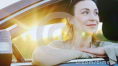 A mulher atrativa olha para fora a janela de carro, retrato Atrás dela são os raios do sol de ajuste Excitador feliz filme
