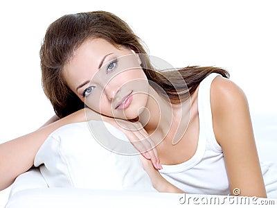 Mulher bonita com a pele limpa que senta-se no sofá