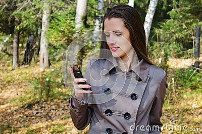 A mulher bonita com um telemóvel na caminhada na madeira