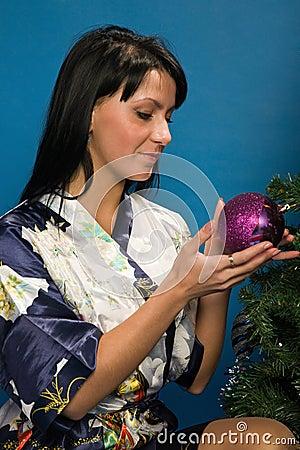 A mulher bonita decora uma árvore de Natal