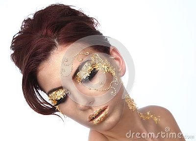 Mulher bonita decorada com os cosméticos da folha de ouro
