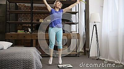 Mulher bonita do ajuste que comemora a perda de peso dentro video estoque
