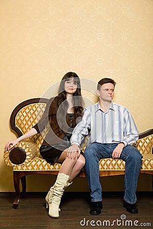 Mulher bonita e homem que sentam-se no sofá no quarto