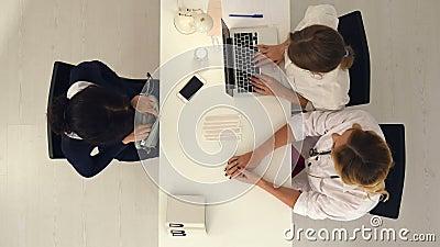A mulher bonita nova dá o salário a dois doutores fêmeas no escritório médico video estoque