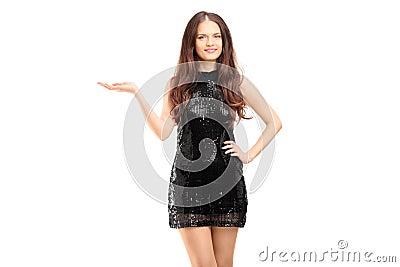 Mulher bonita nova em gesticular preto do vestido elegante