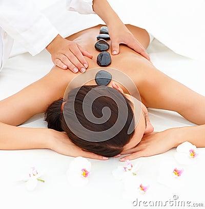 Mulher bonita que recebe a massagem do hotstone em termas