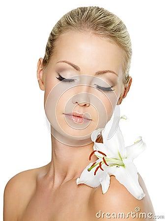 Mulher bonita que relaxa com o lírio branco no corpo