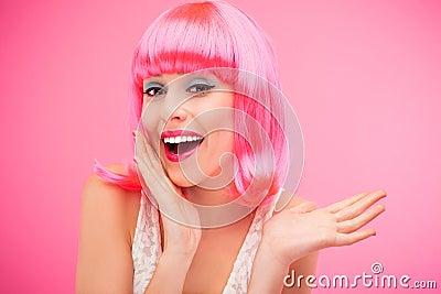 Mulher bonita que veste a peruca cor-de-rosa
