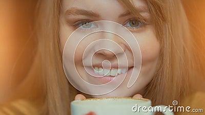 Mulher bonito de sorriso que guarda o copo do café quente nas mãos Inalando o aroma e relaxamento vídeos de arquivo