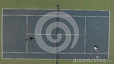 A mulher bonito no vestido e o indivíduo novo no short jogam o tênis na corte filme