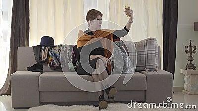 Mulher caucasiana atraente adulta a falar com assinantes através do smartphone Bonita senhora sentada no sofá com bolsa de presen filme