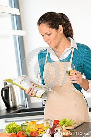 Mulher caucasiano que prepara o cozimento da cozinha da receita dos vegetais