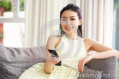 Mulher chinesa nova que presta atenção à tevê no sofá em casa