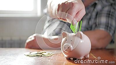Mulher colocando cartão de crédito no banco piggy Conceito de poupança de dinheiro e investimento filme