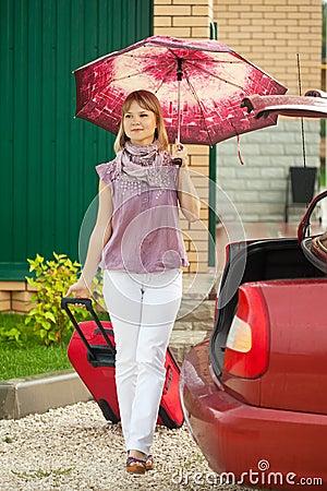A mulher com bagagem vai ao carro