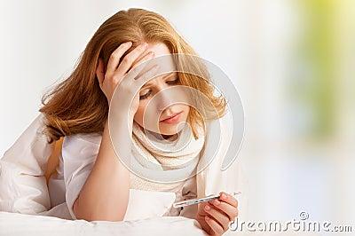 Mulher com frios doentes do termômetro, gripe, febre, dor de cabeça na cama